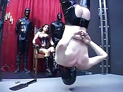 Mistress dominating her slave in front of her other slaves