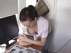 brunette vixen reading a paper in a down blouse
