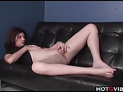 Hot Brunette pleases her pussy while on the couch