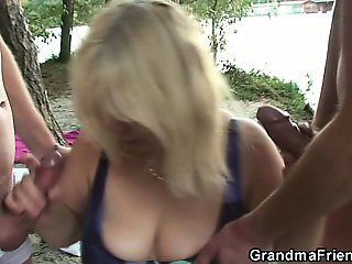 Two dudes bang old bitch from both ends outdoors