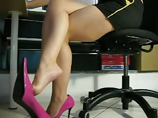 Crossed legs and feet dangling in pink shoes