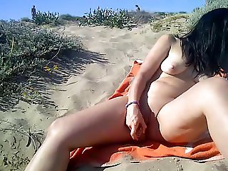 Dildoing on a public nude beach in front of voyeurs