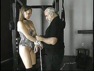Old guy attaches heavy weights to busty brunette's pierced clit in dungeon