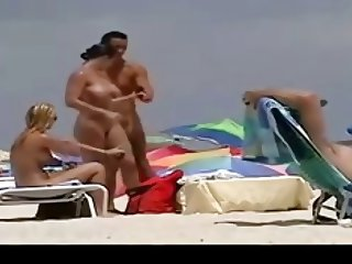two busty girls - brunette and blonde - nude on the beach