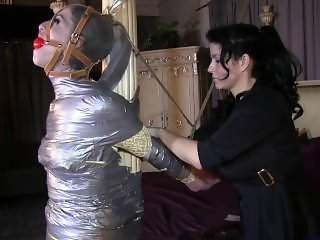 Terra mummified to the post with a gray stocking cap & harness gag