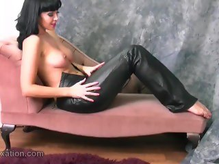 Busty naked babe with hot curvy body puts on her skin tight leather pants