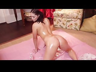 Sexy busty babe stripping with oil and getting naked