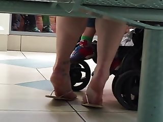 a mum sits and exposes her soles in flip flops