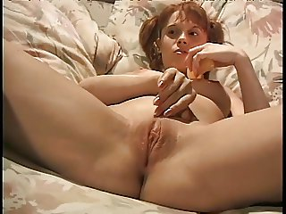 Young redhead sticks her fingers in her panties to rub on her pussy