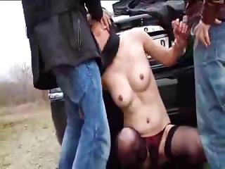 French brunette is sucking and fucking two hard cocks outside