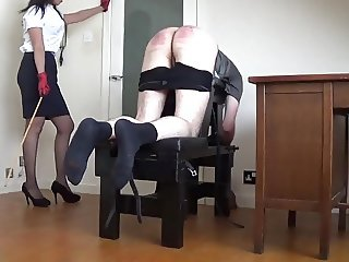 A naughty pupil receives a  caning from Miss Sultrybelle.