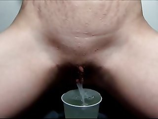 Blonde pissing in a cup