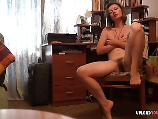 Mature with hairy pussy fingering cunt on a chair