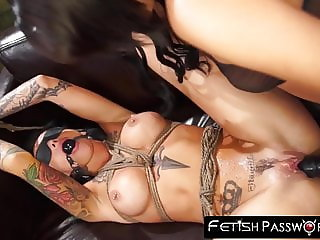 Bound inked sub with large boobs rides a huge black strapon