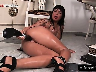 Brunette tramp filling her twat with a large dildo