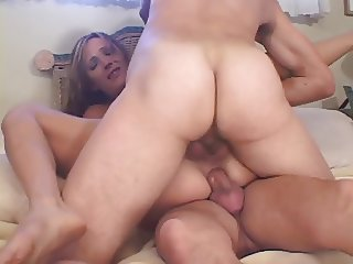 Sexy brunette takes on two cocks in bed