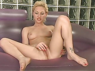 Hot blonde uses vibrator alone on a couch