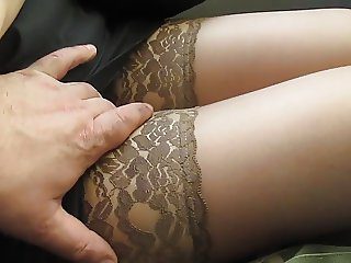 Touching her legs in tan stockings in a bus