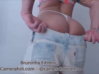 Fitness babe putting tight jeans shorts - Dress and drop tight jeans boot