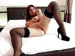Busty babe fucked on a bed in black stockings