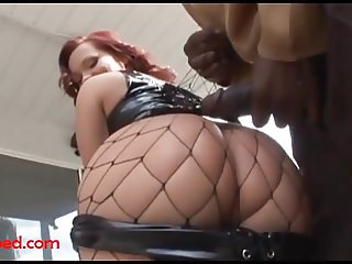 Redhead in fishnets and leather with fake tits takes big bla