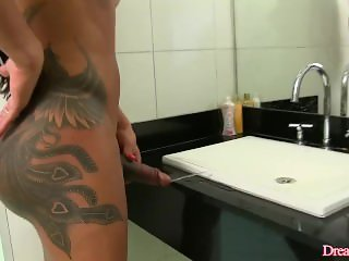 Muscular shemale gets naked and urinates