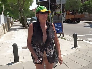 Mature walking down the street showing charms