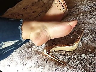 Slightly rough feet and golden sandals play