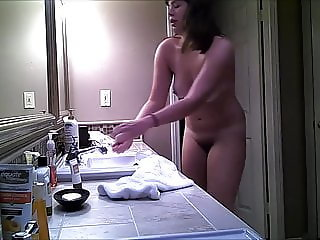 Teen sister stripping off swimsuit in bathroom