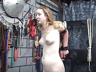 Dude takes vibrator to young bondaged blonde's pale shaved pussy