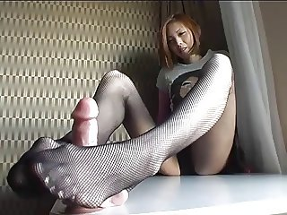 Japanese leg model does a footjob with a plastic cock.