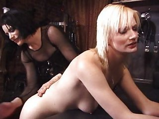 Submissive blonde spanked by her two mistresses