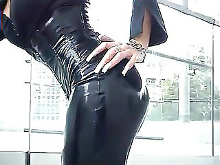 Blonde lady with long black shiny coat and skirt