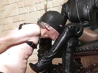 Leather Mistress and man licking her boots