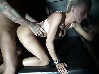 Sexy swinger couple in a glory hole booth