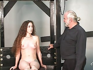Long haired hussy is bent over sex device and gets her ass caned