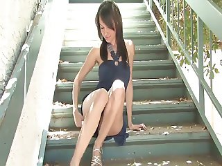 Busty brunette plays with a vibrator on the stairway