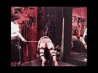 Mistress clad in sexy rubber, canes her slave to the limit.
