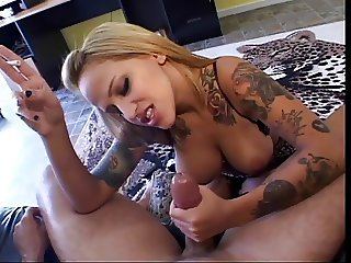 Tattooed chick with awesome tits gives an awesome handjob while smoking