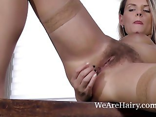 Jehanna strips naked and fingers her hairy pussy