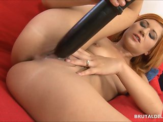 Strawberry blonde beauty swallowing a big brutal dildo