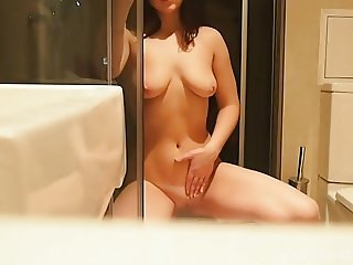 Brunette gets naked and masturbates in the bathroom