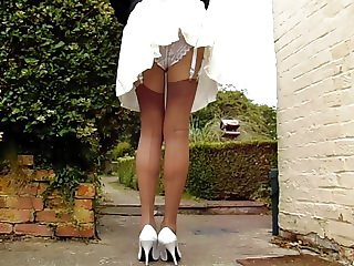 Tan Stockings With Pleated Skirt On A Windy Day