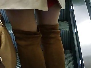 Sexy legs in pantyhose and overknee boots on escalator