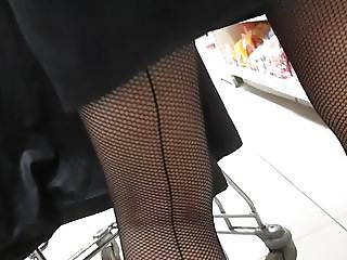Touching her legs in a seamed fishnet stockings in market
