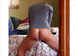 Riding her dildo on the edge of the bed