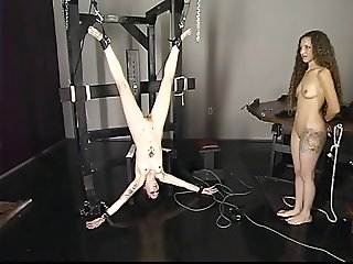 Blonde watches while brunnette is tortured upside down.