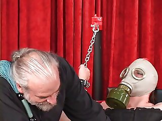 Shackled heavy woman in gas mask bound to bench with her shaved pussy wide open