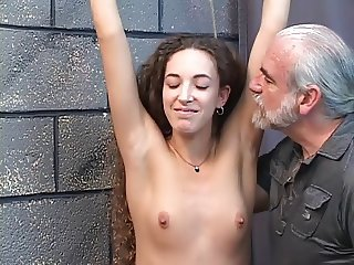 Beautiful young shaved pussy brunette is restrained in dungeon for spanking