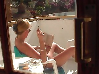Topless tart in tenerife flashes her pussy